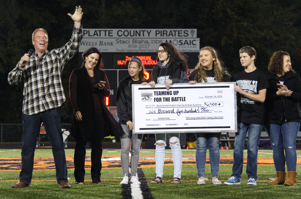 Contributed photo Kansas City Royals broadcaster Rex Hudler, left, and his wife Jennifer Hudler, second from left, received a donation to their charity Team Up for Down Syndrom from Platte County High School students (from left) Brittany Alvarado, Jewel Fivecoat, McKennah Houlahan and Connor Green and Future Business Leaders of America advisor Hannah Kasner, right, at halftime of the Platte County vs. Kearney football game on Friday, Oct. 14 at Pirate Stadium.