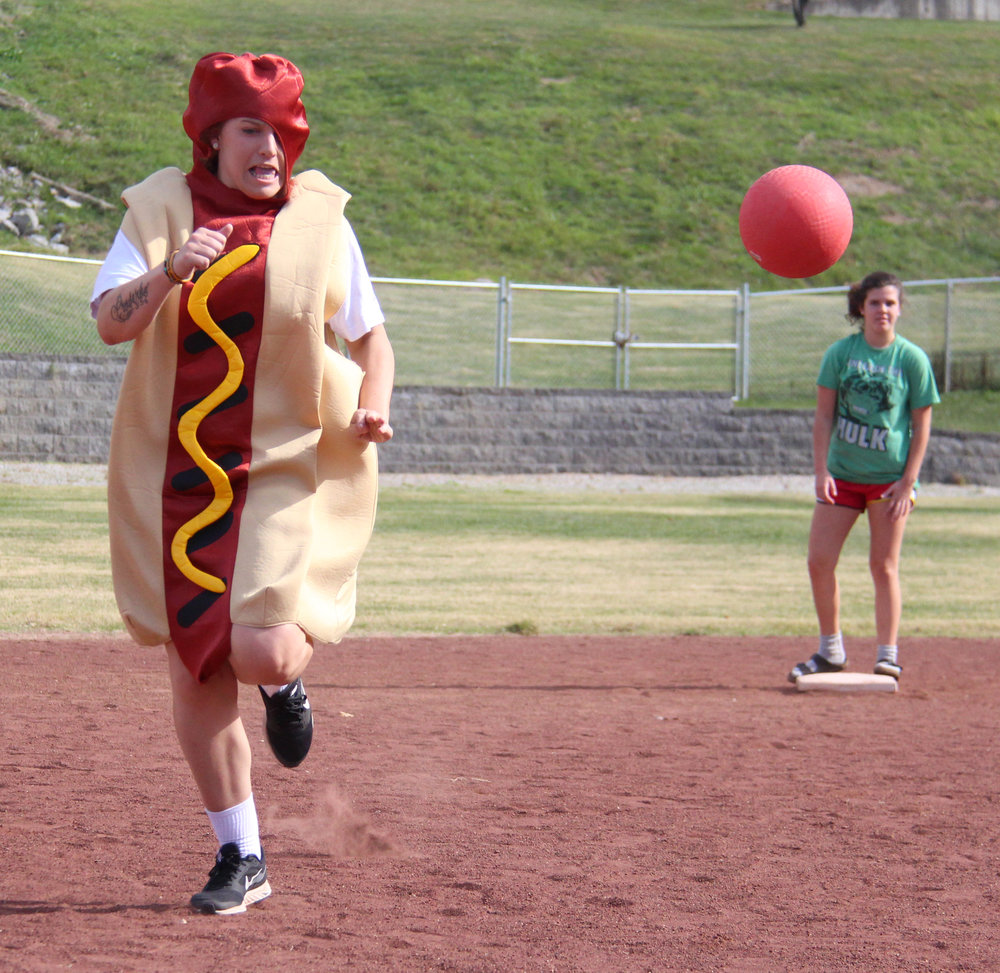ROSS MARTIN/Citizen photo Taylor Sellers, left, runs to third base while trying to avoid a throw during one of the costume kickball games Saturday, Oct. 29 at Harrel Ferrel Park. Proceeds from the event donated to the Jaros family.