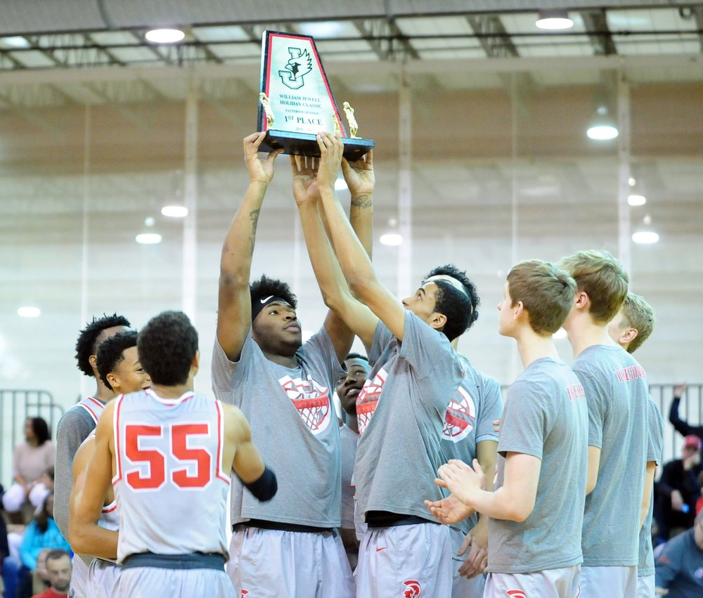 NICK INGRAM/Citizen photo Park Hill players hold up their championship trophy after defeating Raytown in the Patterson Division championship game of the William Jewell Holiday Classic on Friday, Dec. 30 at William Jewell College in Liberty, Mo.