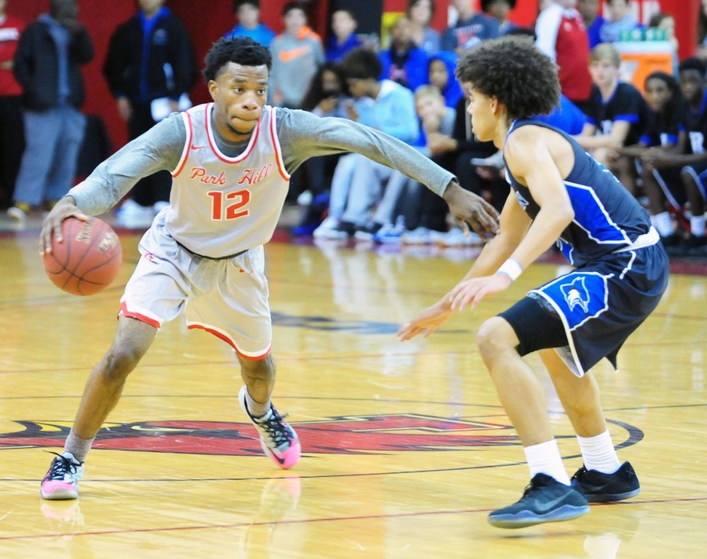 NICK INGRAM/Citizen photo Park Hill senior Dru Smith dribbles past a Raytown defender during the Patterson Division title game on Friday, Dec. 30 in Liberty, Mo.