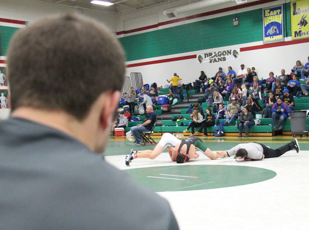 ROSS MARTIN/Citizen photo Mid-Buchanan assistant coach Jake Rumpf, front, looks on as Rotterman pins Maryville's Jackson Sanders in the 160 championship match.