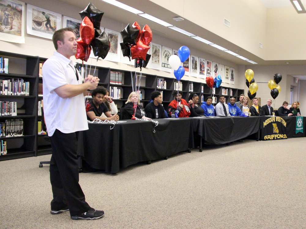 ROSS MARTIN/Citizen photo Park Hill football coach Josh Hood, left, speaks during a signing ceremony Wednesday, Feb. 1 in the school's media center to honor six college signees.