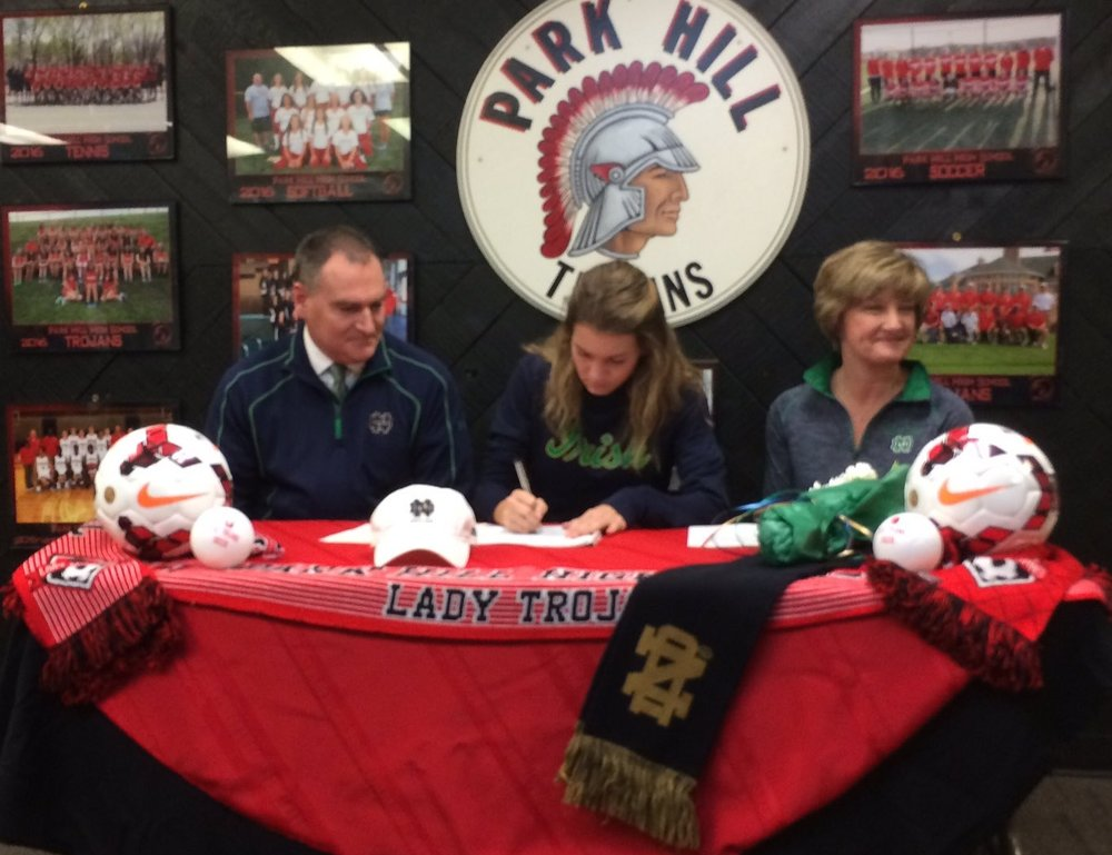 Contributed photo Park Hill senior Jenna Winebrenner, center, signs her national letter of intent to play soccer at Notre Dame during a ceremony Wednesday, Feb. 1 at Park Hill High School in Kansas City, Mo.