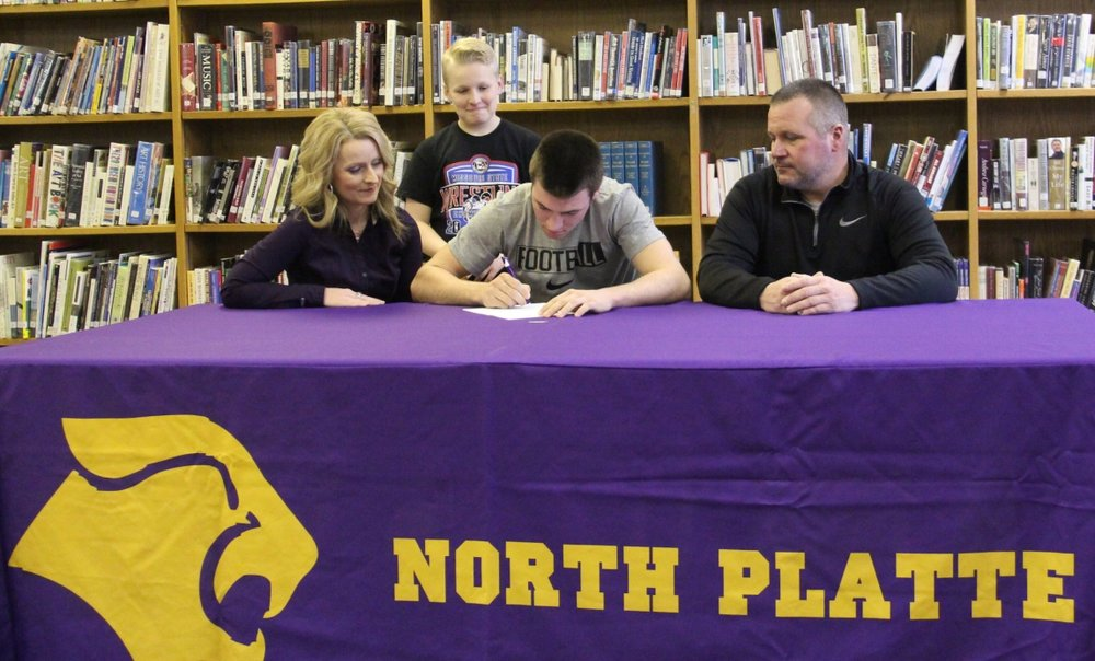 ROSS MARTIN/Citizen photo North Platte senior Parker Rotterman, center, signs to play college football at Avila during a ceremony Tuesday, Feb. 7 at North Platte High School in Dearborn, Mo.