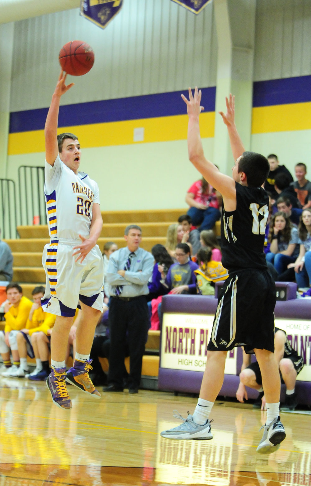 NICK INGRAM/Citizen photo North Platte sophomore Hunter Hendricks, left, jumps to make a pass over a Lathrop defender during a KCI Conference game Friday, Feb. 3 at North Platte High School in Dearborn, Mo.