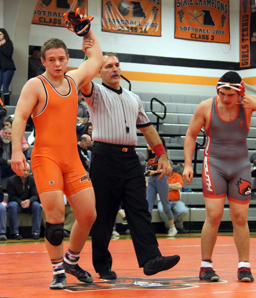 ROSS MARTIN/Citizen photo Mark Mundell raises the arm of Platte County senior Casey Jumps after his victory in a 220-pound match against Raytown South's Braden Tofaeono, right, in a dual Thursday, Feb. 2 at Platte County High School.