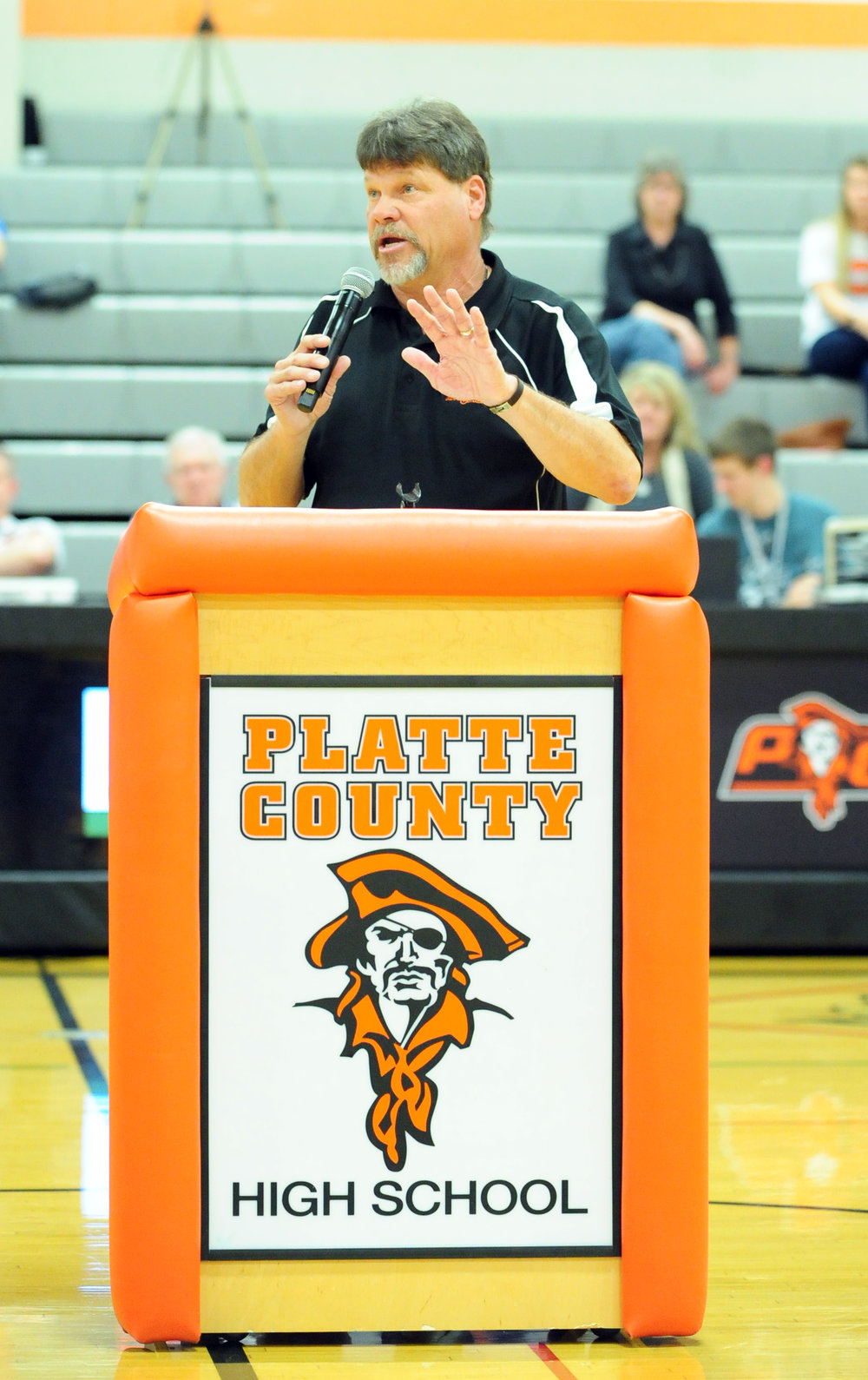 NICK INGRAM/Citizen photo Former Platte County High School coach and athletic director Greg Jaros speaks during the Pirate Hall of Fame induction ceremony on Friday, Feb. 17 at Platte County High School. BOTTOM: Former coach Jan Patterson, right, hugs Jaros.