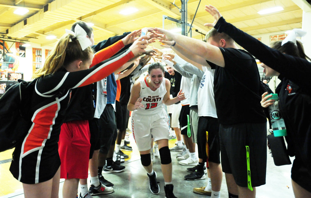NICK INGRAM/Citizen photo Platte County students made a tunnel with their arms for the Platte County girls basketball team, including senior Amy Lett, to run through after their 57-32 victory over Raytown South on Friday, Feb. 20 at Platte County High School.