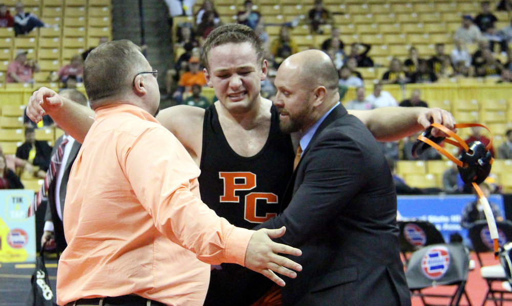 ROSS MARTIN/Citizen photo Platte County senior Casey Jumps, center, goes to hug head wrestling coach Reggie Burress, left, and assistant Gabe Middleton after Jumps won the Class 3 Missouri State Wrestling Championships' 220-pound championship match Saturday, Feb. 18 at Mizzou Arena in Columbia, Mo.