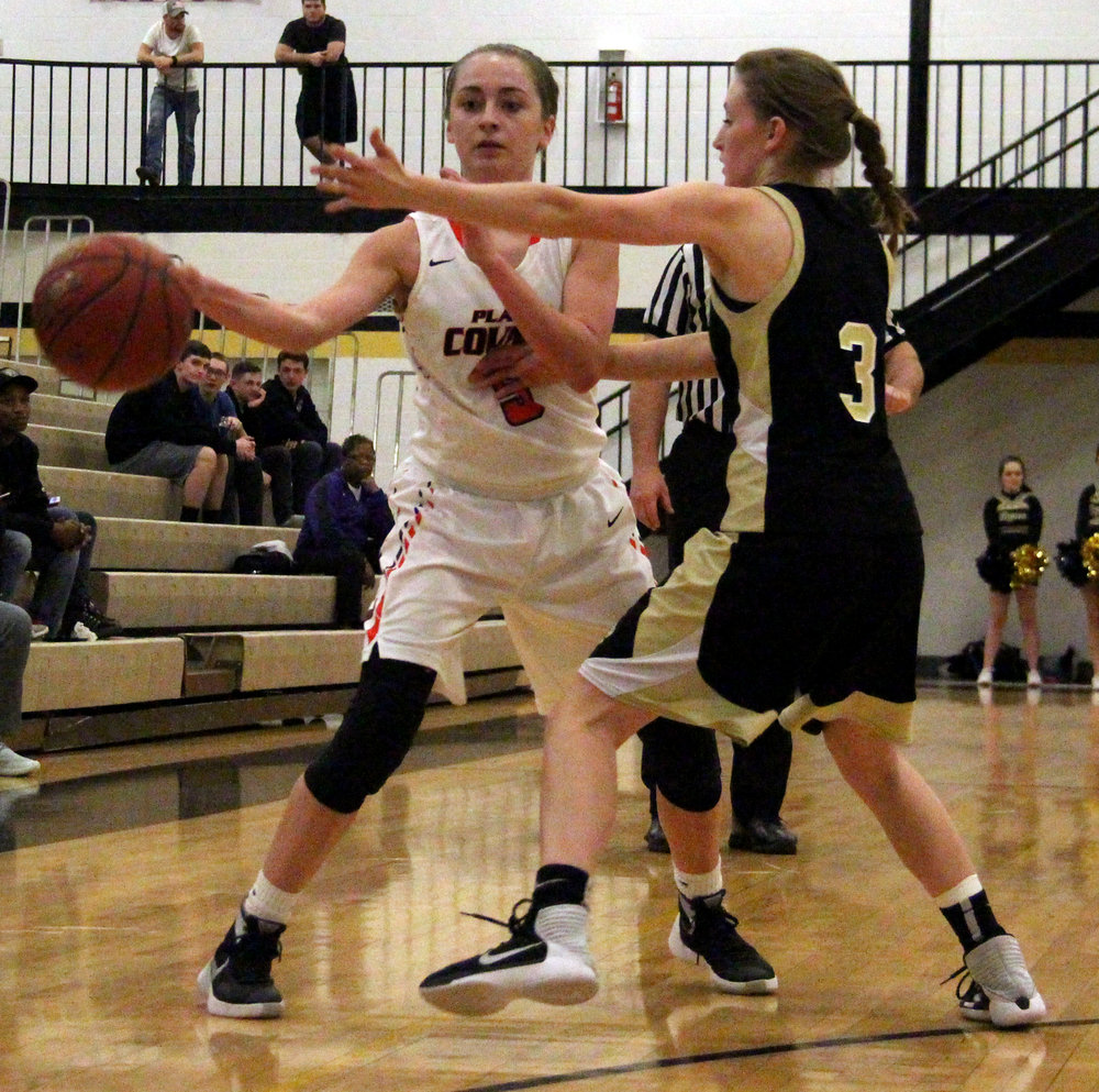 ROSS MARTIN/Citizen photo Platte County sophomore guard Taylor Farr, left, makes a pass around an Excelsior Springs defender in a Class 4 District 15 semifinal Monday, Feb. 27 at Excelsior Springs High School in Excelsior Springs, Mo.