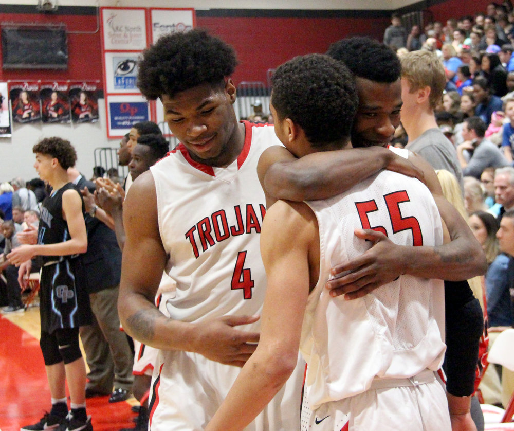 ROSS MARTIN/Citizen photo Park Hill senior Dru Smith hugs junior teammate Ronnie Bell (55) while celebrating with senior Chester Graves (4) late in the Class 5 District 16 championship game Friday, March 3 at Park Hill High School in Kansas City, Mo.