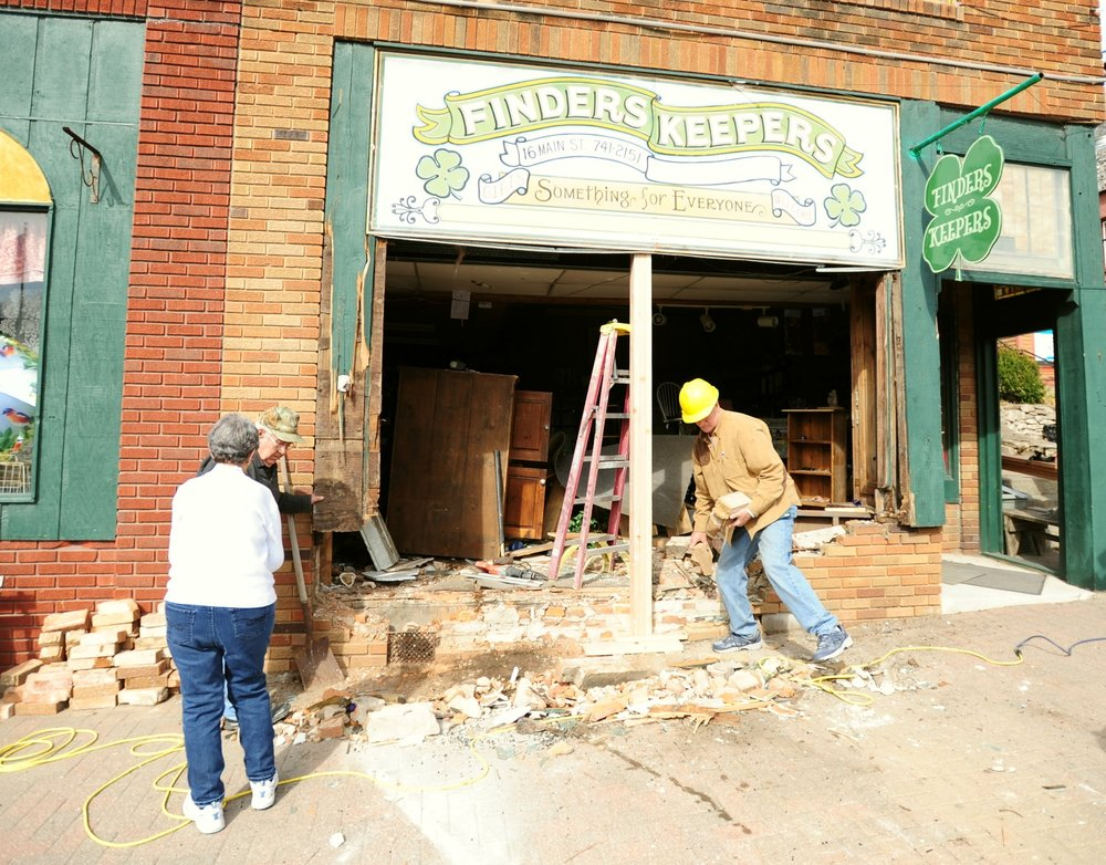 NICK INGRAM/Citizen photo Workers try to stabilize Finders Keepers gift shop Friday, March 17 at 16 Main Street in Parkville, Mo. after a man fleeing from police apparently lost control of his SUV earlier in the morning and crashed through the front of the building.