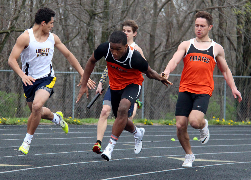 ROSS MARTIN/Citizen photo Platte County senior TJ Guillory, right, completes a handoff to senior teammate Ahmaad Holt during a sprint medley relay in the newly established Pirate Relays held Monday, April 3 at Pirate Stadium.