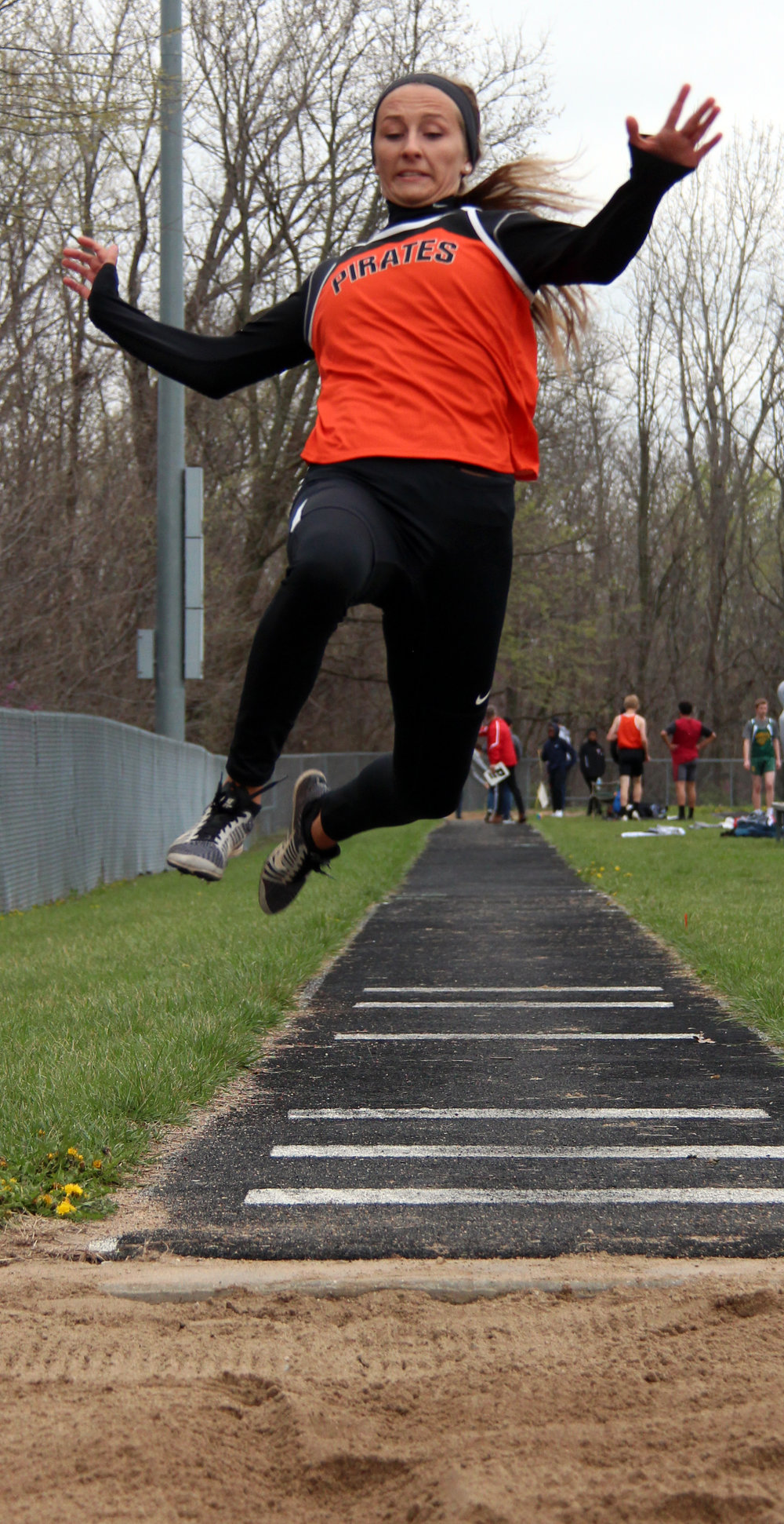 ROSS MARTIN/Citizen photo Platte County senior Tori Farr flies through the air in a long jump attempt during Pirate Flight Night on Friday, March 31 at Pirate Stadium.