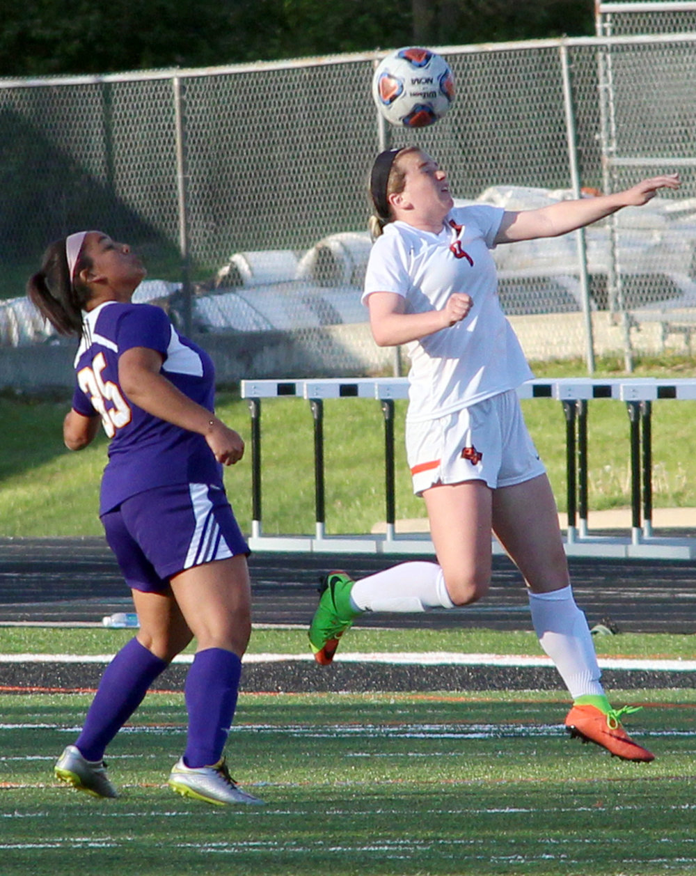 ROSS MARTIN/Citizen photo Platte County senior midfielder Kianna Castro, right, heads the ball upfield against Kearney on Monday, April 17 at Pirate Stadium.