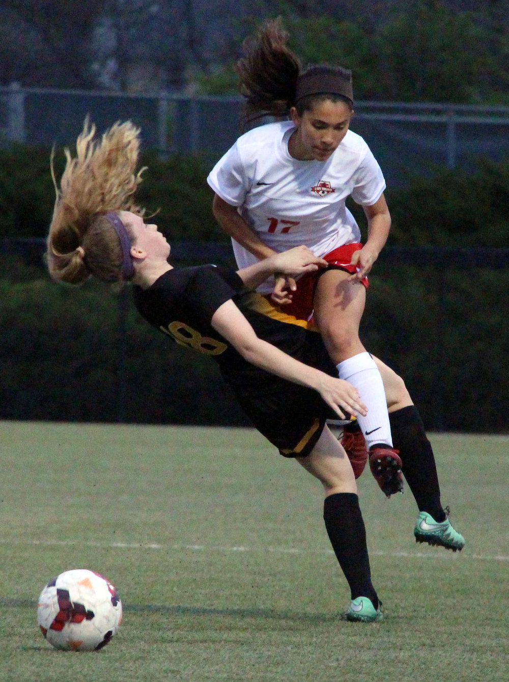 ROSS MARTIN/Citizen photo Park Hill sophomore forward Ayana Weissenfluh clatters into a St. Teresa's Academy defender during a match Wednesday, April 12 at Park Hill District Soccer Complex in Riverside, Mo.