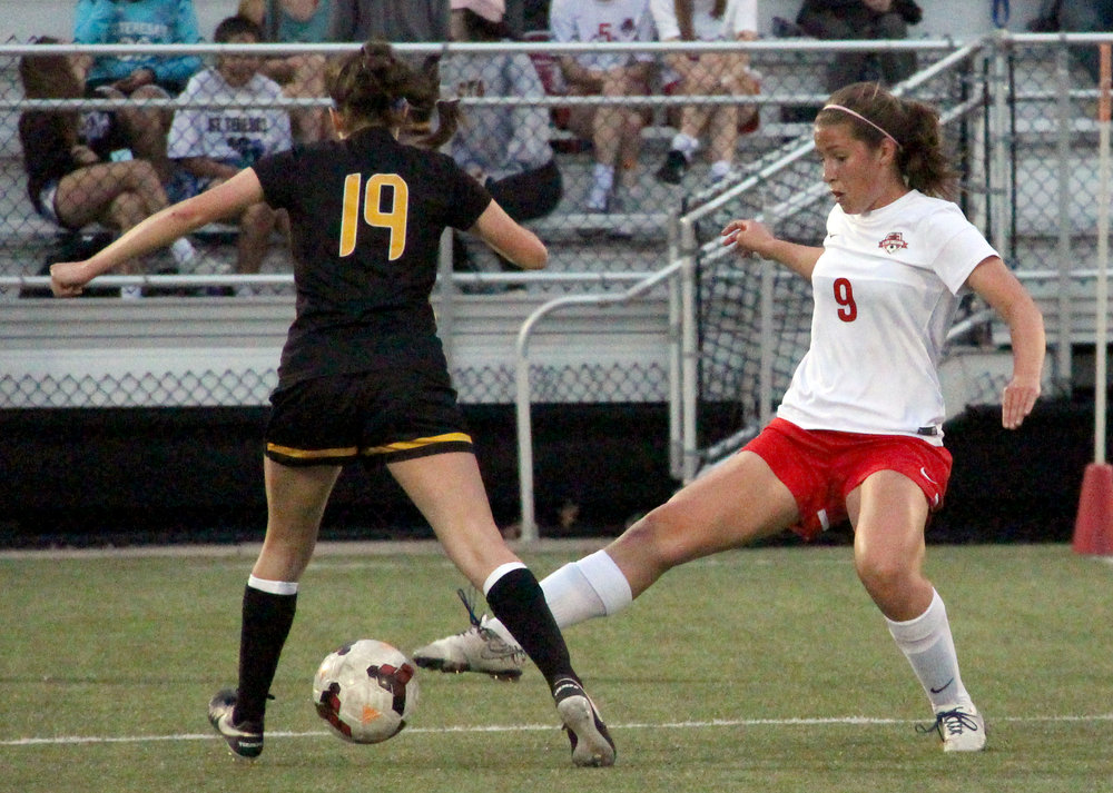 ROSS MARTIN/Citizen photo Park Hill freshman Grace Wineinger (9) pokes the ball loose from a St. Teresa's player Wednesday, April 12 at Park Hill District Soccer Complex in Riverside, Mo.