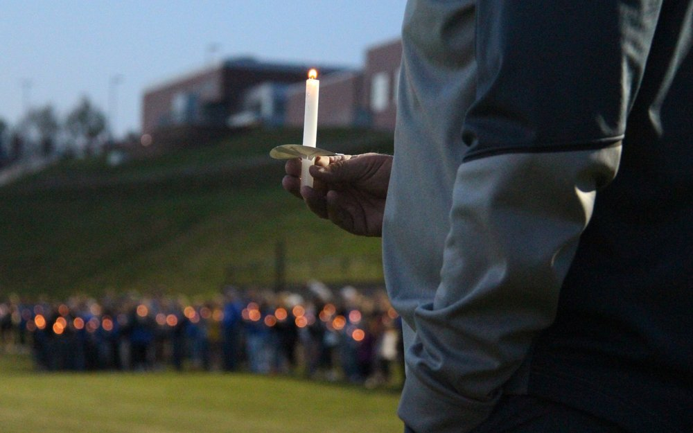 ROSS MARTIN/Citizen photo A man holds a candle during a vigil held Thursday, April 20, the day after the fatal crash that claimed the life of Nate Danneman, at old Rudolph Eskridge Stadium in Weston, Mo. Hundreds attended.