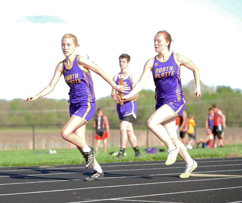 NICK INGRAM/Citizen photo North Platte junior Gracie Roach, right, hands the baton to junior McKenna Fulton in the 4x200-meter relay during the Christian Invitational on Thursday, April 20 at Christian Field in St. Joseph, Mo.