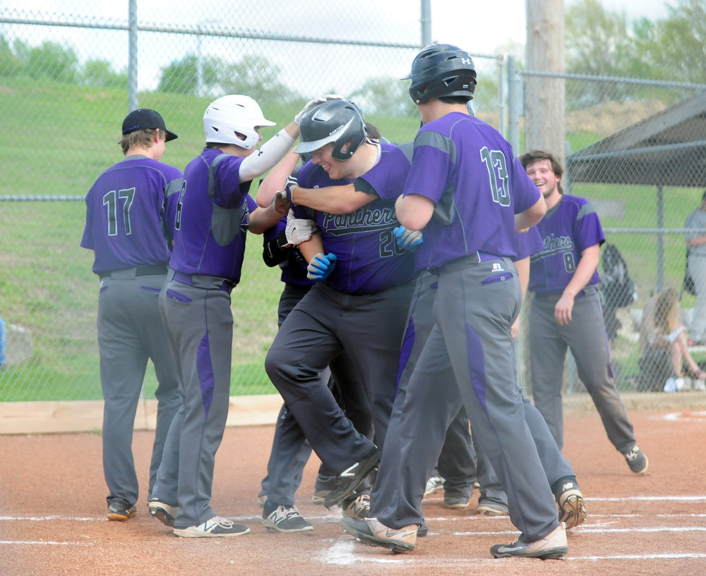 NICK INGRAM/Citizen photo North Platte teammates mob Garrett Lamar, center, after he hit a grand slam in the first inning against West Platte on Wednesday, April 19 at Benner Park in Weston, Mo.