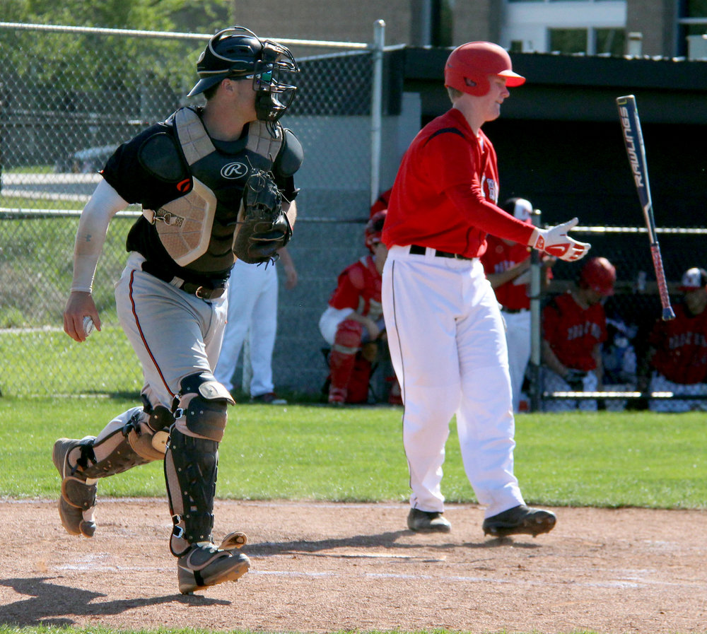 ROSS MARTIN/Citizen photo Platte County senior catcher Justin Mitchell, left, jogs off the field after Park Hill's Grant Mertz, right, struck out in the first inning of the Northland Tournament's fifth-place game Thursday, April 20 at Park Hill High School in Kansas City, Mo..