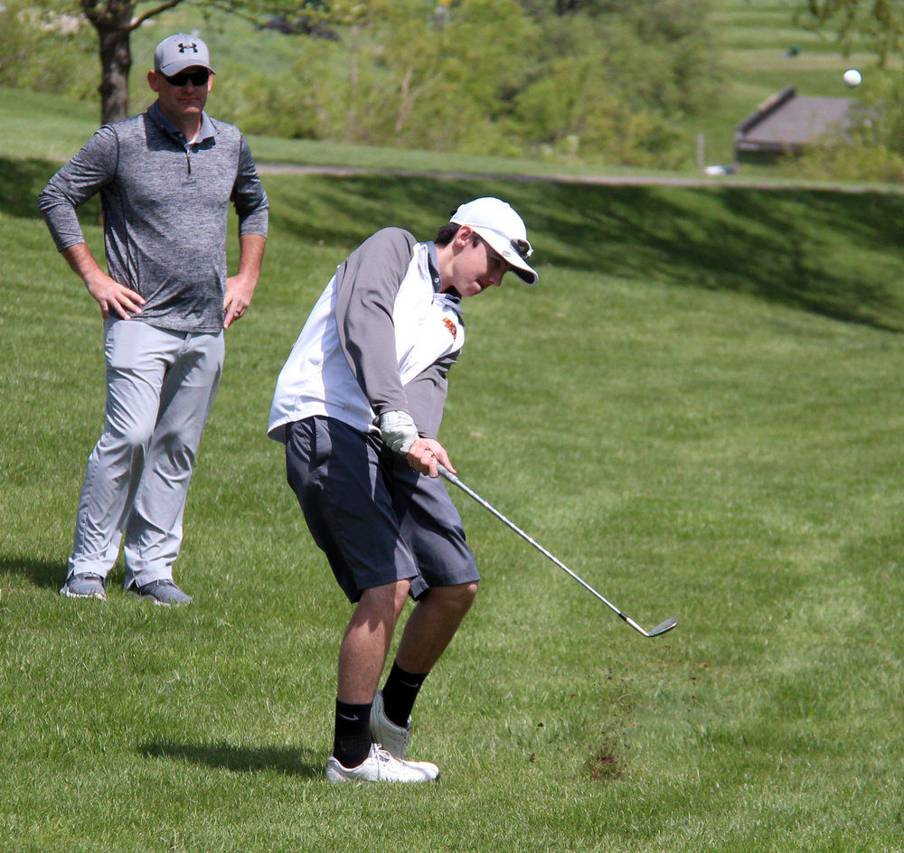 ROSS MARTIN/Citizen photo Platte County freshman Logan Hessemyer hits a chip shot to the 10th green during the Suburban Conference Blue Division Championships on Monday, April 24 at Shiloh Springs Golf Course. Platte County coach Trevor Short watches at rear.