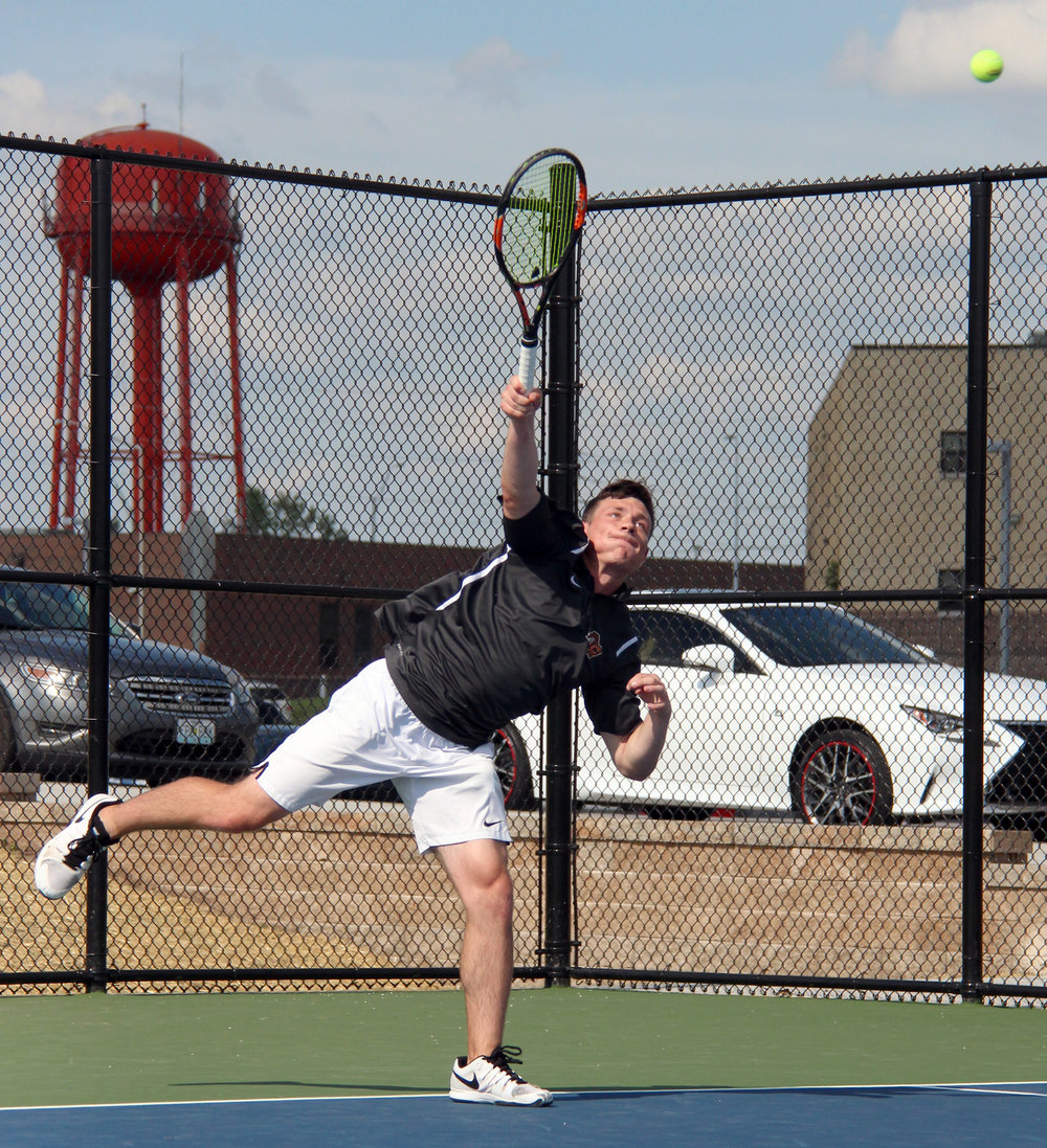 ROSS MARTIN/Citizen photo Platte County senior Spencer Kunz hits a serve with the famous Platte City water tower in the background of the school's new home facility during a doubles match in a Class 2 District 16 semifinal with North Kansas City on Tuesday, May 9.