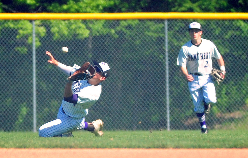 NICK INGRAM/Citizen photo Park Hill South senior center fielder Andrew Aswegan, left, slides after a fly ball against Platte County on Saturday, May 6 at Park Hill South High School in Riverside, Mo.