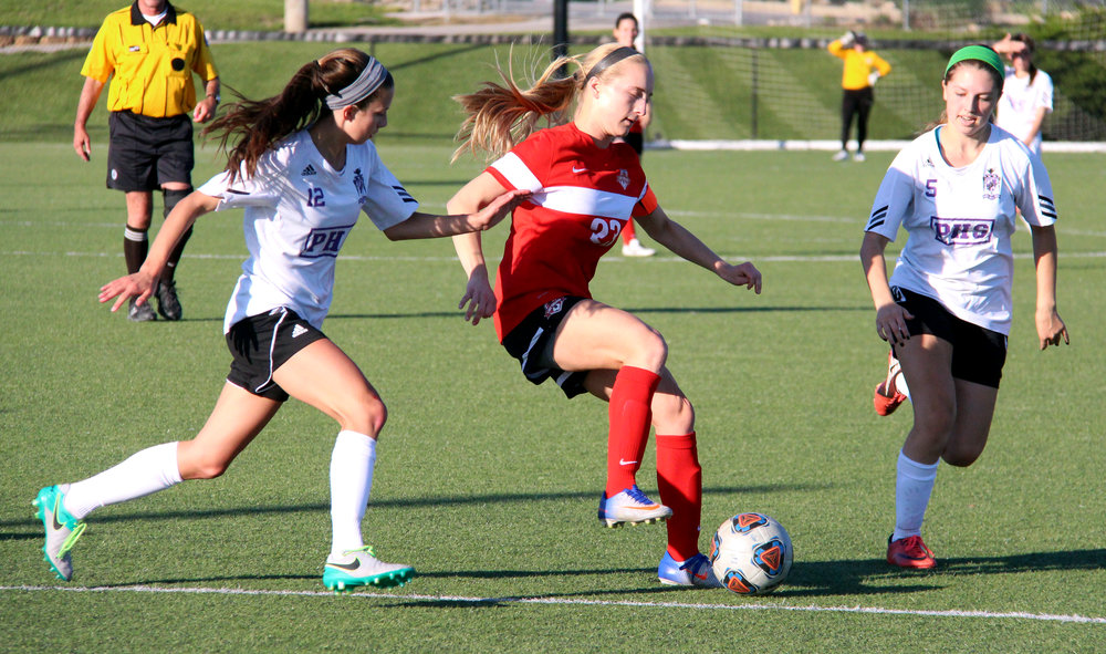 ROSS MARTIN/Citizen photo Park Hill junior forward Alison Walls, center, dribbles in between Park Hill South defenders Lexi Maddox and Marquese Oder on Saturday, May 6 at Park Hill District Soccer Complex in Riverside, Mo.