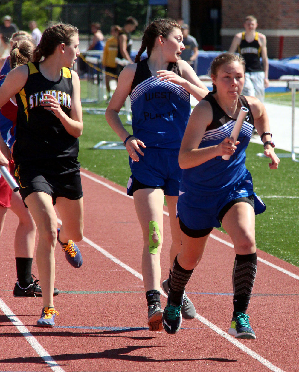ROSS MARTIN/Citizen photo West Platte junior Rachel Heili (right) takes the baton from sophomore Lindsay Goodwin in the 4x400-meter relay Saturday, May 6 in the Class 1 District 8 track meet held at Rudolph Eskridge Stadium in Weston, Mo.