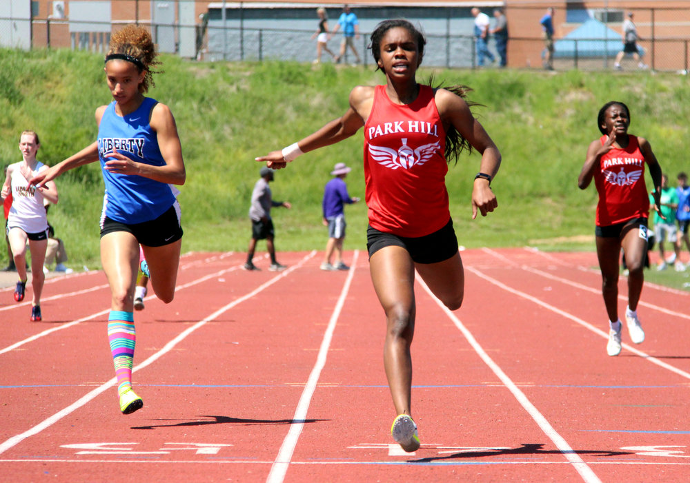 ROSS MARTIN/Citizen photo Park Hill junior Taiya Shelby, center, finishes first in the 400-meter during the Class 5 District 8 meet Saturday, May 13 at Park Hill District Stadium in Kansas City, Mo. At right, sophomore teammate Manuela Ngo Tonye Nyemeck races to third place.