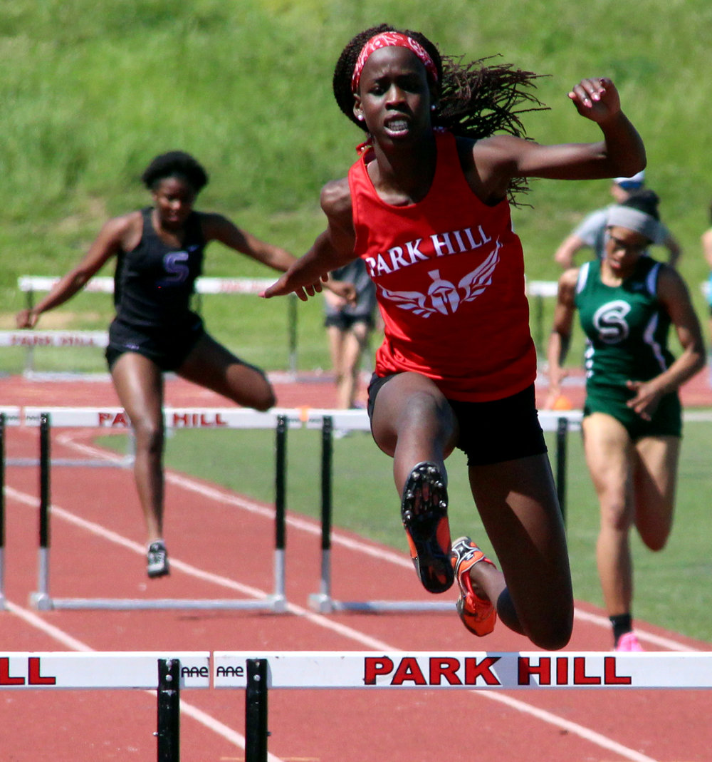 ROSS MARTIN/Citizen photos Park Hill senior Ariet King clears a hurdle on the way to a win in the 300-meter race.