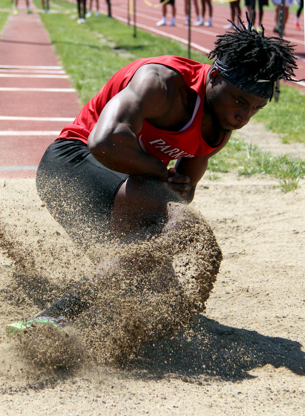 ROSS MARTIN/Citizen photo Park Hill senior Papay Glaywulu hits the sand on a triple jump attempt during the Class 5 District 8 meet Saturday, May 13 at Park Hill District Stadium in Kansas City, Mo.