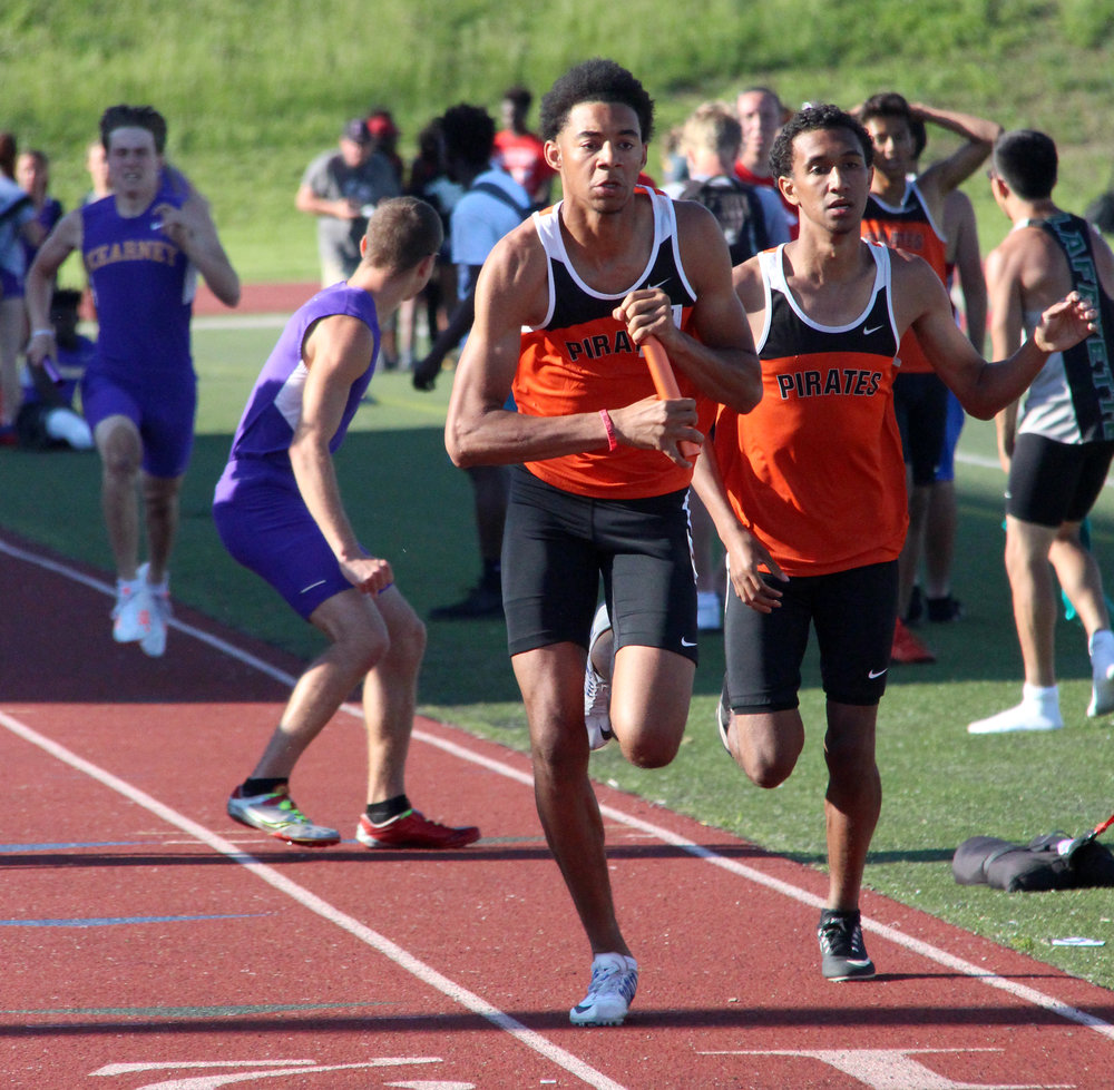 ROSS MARTIN/Citizen photo Platte County junior John Watts (left) takes the baton from junior Matthew Phillips in the 4x400-meter relay during the Class 4 District 8 meet Saturday, May 13 at Park Hill District Stadium in Kansas City, Mo.