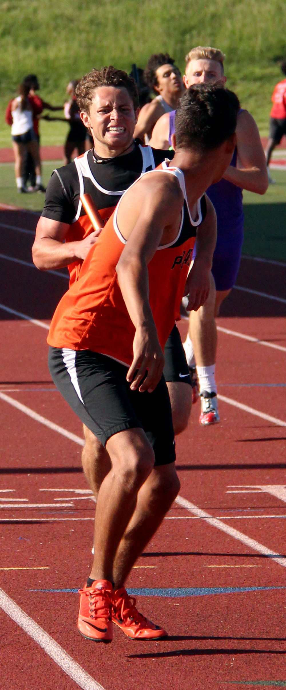 ROSS MARTIN/Citizen photo Platte County senior TJ Guillory, rear, hands the baton to junior Matthew Phillips in the 4x400 relay Saturday, May 13 during the Class 4 District 8 meet at Park Hill District Stadium in Kansas City, Mo. Matthew Phillips, a junior at right, is closing the gap to finish second.