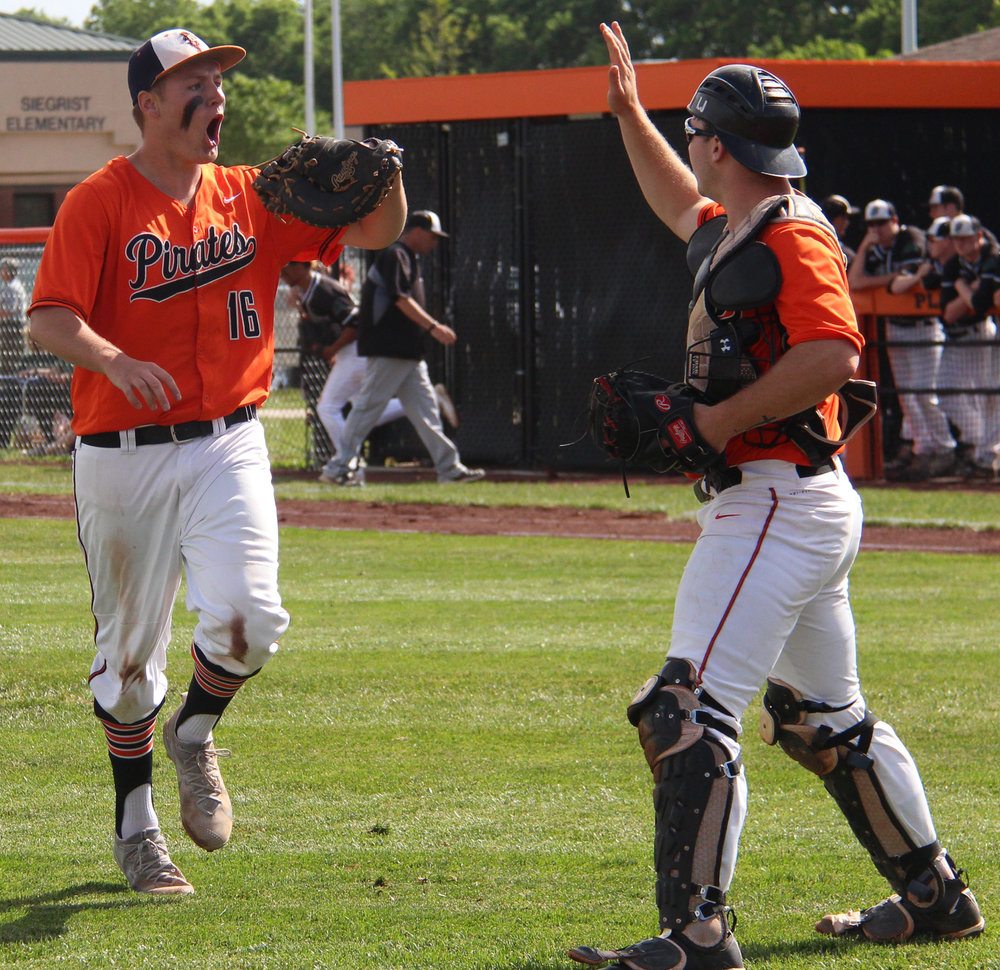 ROSS MARTIN/Citizen photo Platte County senior first baseman Austin Gammill, left, celebrates with catcher Justin Mitchell after Gammill's diving stop helped the Pirates escape a first-inning jam in the Class 5 District 16 championship game Wednesday, May 17 at Platte County High School.