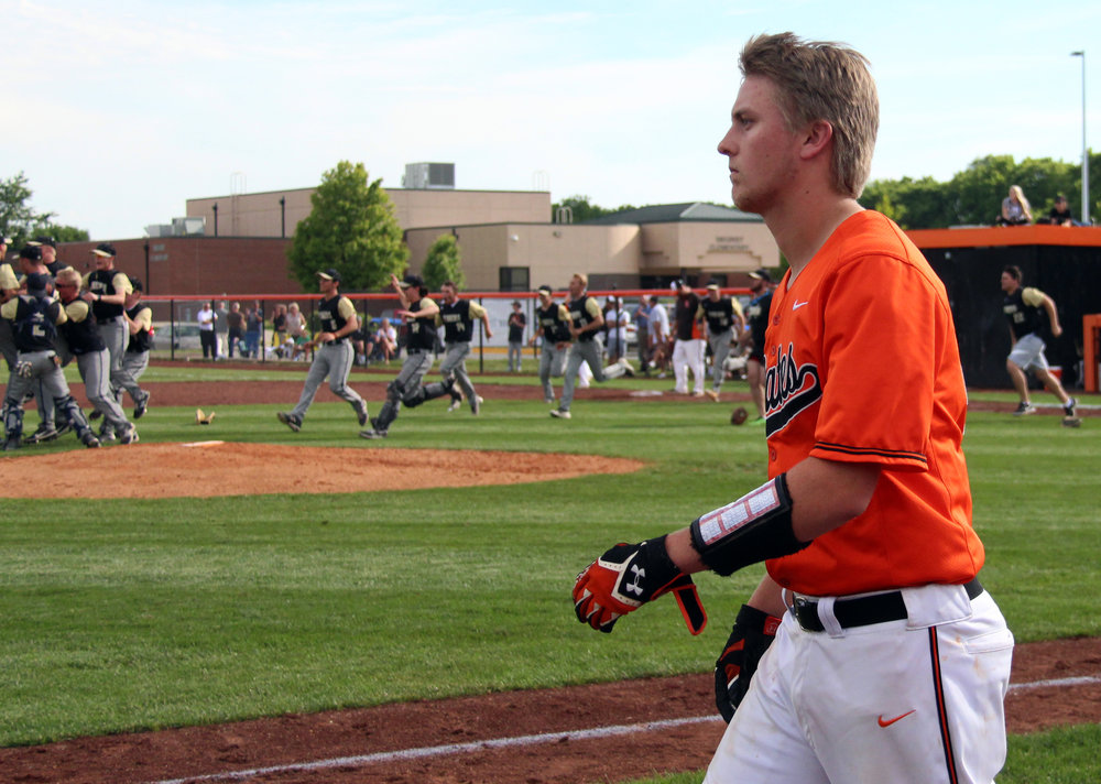 ROSS MARTIN/Citizen photo Platte County senior Jared Wilson walks out of the dugout as Lee's Summit players celebrate a 1-0 win in a Class 5 quarterfinal Thursday, May 25 at Platte County High School.
