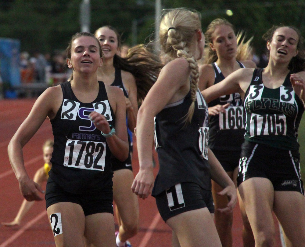 ROSS MARTIN/Citizen photo Park Hill South senior Jasmine Crawford, left, finishes second in the 800 on Saturday night with sophomore teammate Emma Roth coming in fifth right behind her.