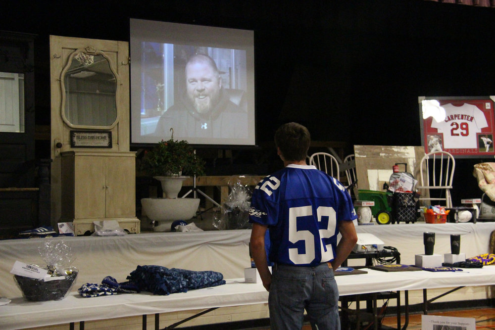 ROSS MARTIN/Citizen photo West Platte senior Julian Trelow watches a video tribute to deceased football coach Nate Danneman, who was killed in a car accident this past April, during a fundraiser dinner and auction for Danneman's family Saturday, June 10 at North Platte Junior High School in Dearborn, Mo.