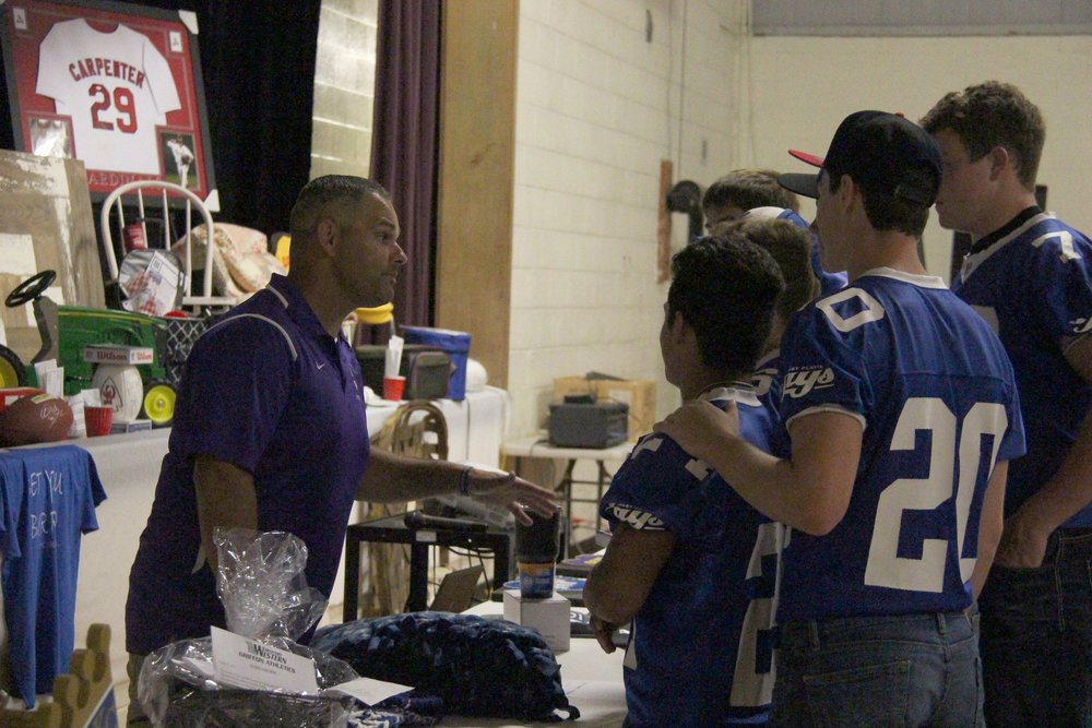 ROSS MARTIN/Citizen photo North Platte football coach Josh Rodriguez, left, talks with a group of West Platte football players during the event.