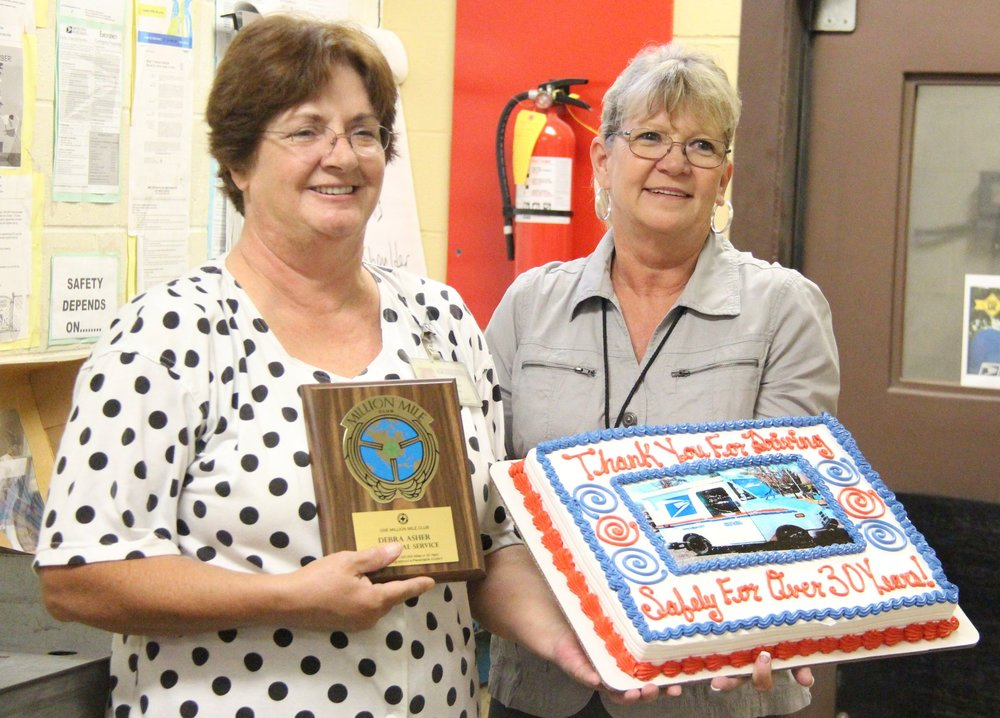 "ROSS MARTIN/Citizen photo Platte City Post Office postmaster Marla Eschbacher, right, presented long time mail carrier Debbie Asher with a National Safety Council ""Million Mile Award"" for her service. Asher has spent 34 years as a carrier in Platte City, including 26 in a full-time capacity. The award goes to workers who have logged one million miles of driving or at least 30 years with driving as a daily duty with no accidents."