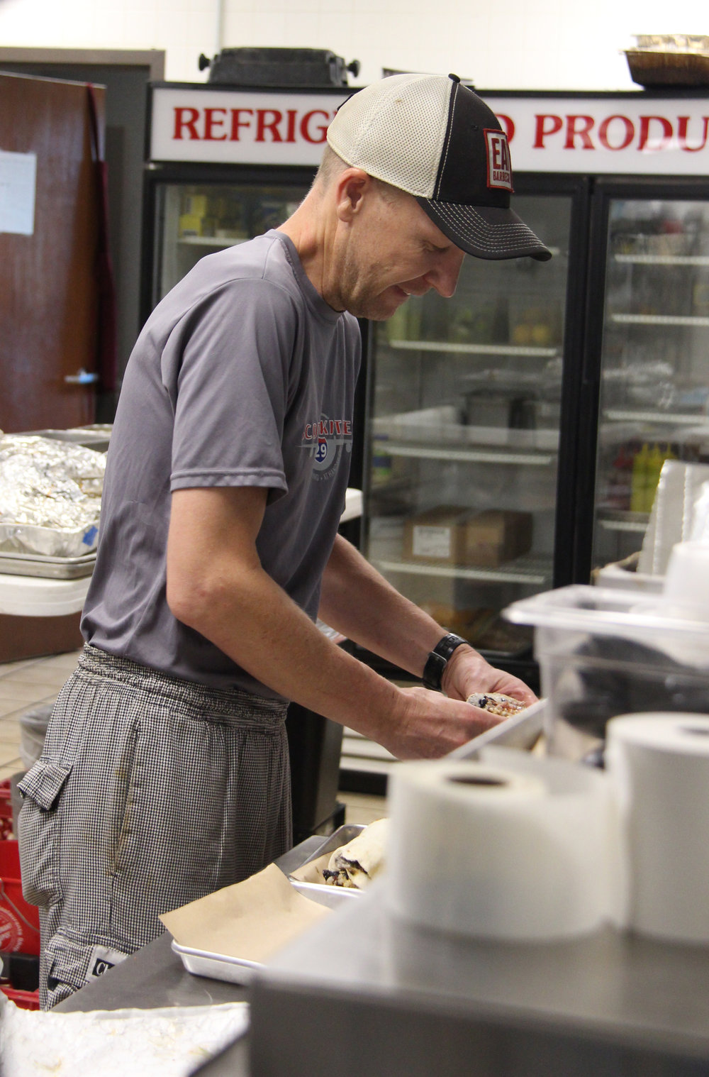 Contributed photo Scott Umscheid prepares a burrito Tuesday, Aug. 1 at his newly opened restaurant Scott's Kitchen and Catering at Hangar 29, located on NW Ambassador Drive in central Platte County.