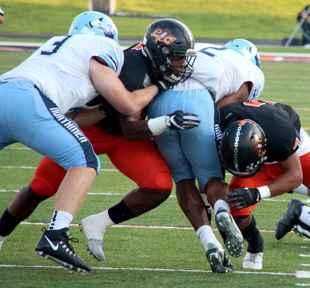 ROSS MARTIN/Citizen photo Platte County seniors Michael Smith (center left) and Kobe Cummings (right) make a tackle in the first half against Oak Park on Friday, Aug. 25 at Pirate Stadium.