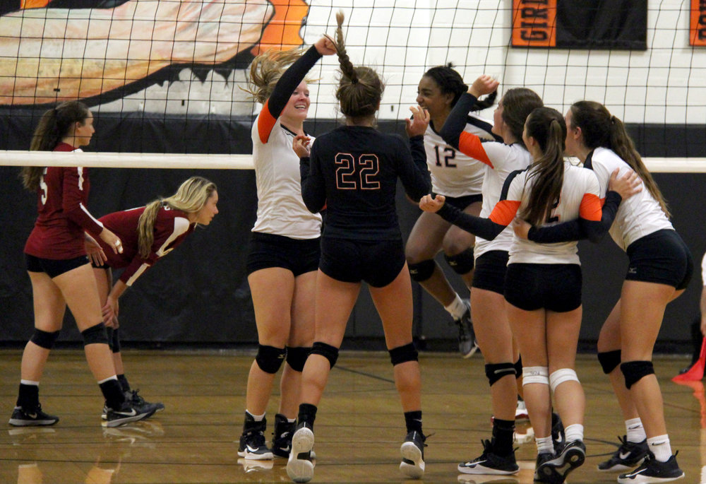 ROSS MARTIN/Citizen photo Platte County players, including Lauren Walker (left) and PJ Curry (12) celebrate a five-set victory against Lee's Summit North on Monday, Aug. 28 at Platte County High School.