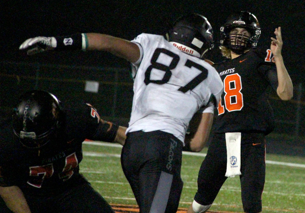 ROSS MARTIN/Citizen photo Platte County senior quarterback Tanner Clarkson (18) looks to throw over the outstretched arm of Staley defender Zach Elam during a game Friday, Sept. 1 at Pirate Stadium.