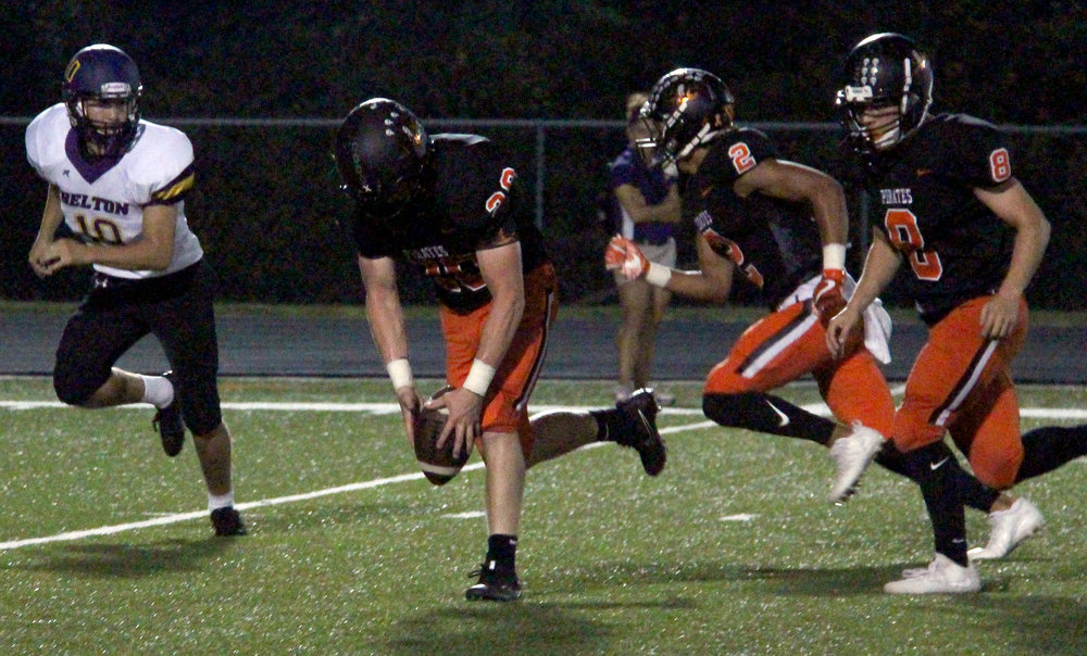 ROSS MARTIN/Citizen photo Platte County senior linebacker Dakota Schmidt, center, scoops up the ball after he blocked a punt in the first half against Belton on Friday, Sept. 15 at Pirate Stadium. Schmidt scored his third career touchdown on the play.
