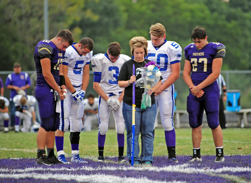 North Platte seniors Austin Snook, left, and Remington Wilson, right, presented Tabitha Danneman with an honorary Tobacco Stick along with West Platte seniors Grant Eagen (5), Gavin Raney (3) and Cole Whalen (50) prior to a moment of silence before the game.