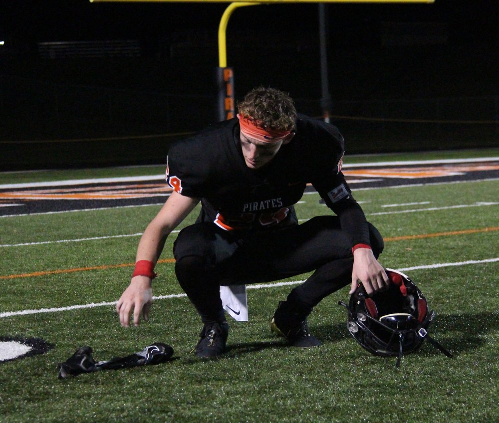 ROSS MARTIN/Citizen photo  Platte County senior JP Post bends down to the Pirate Stadium turf to take off his helmet and gloves following a 35-28 overtime win against Liberty on Friday night.