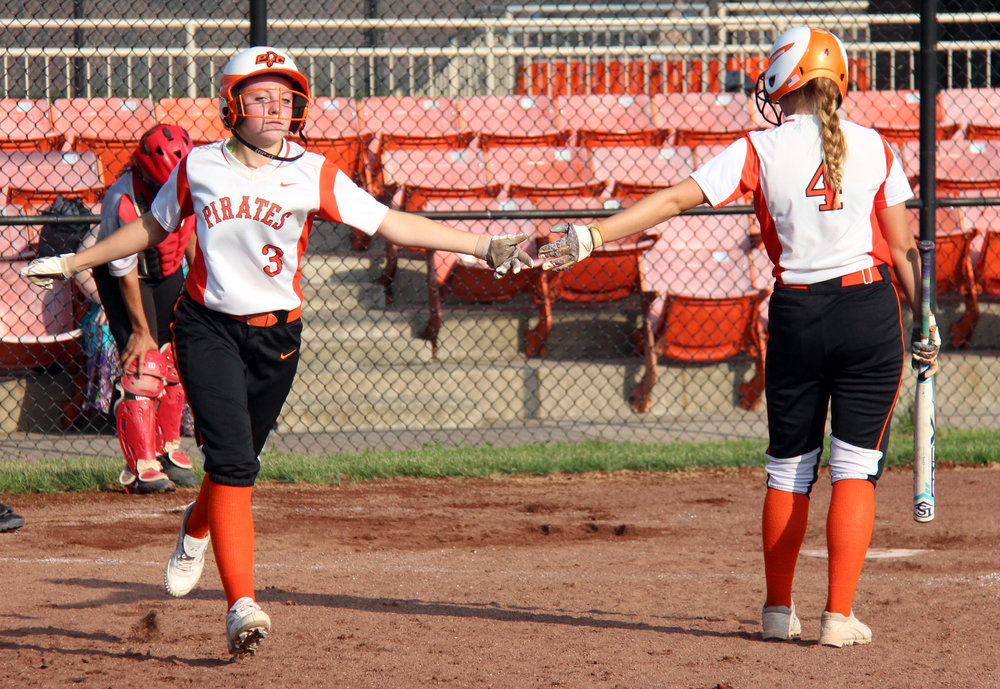 ROSS MARTIN/Citizen photo Platte County sophomore Gracie Erickson (3) slaps hands with junior Janessa Barmann (4) after Erickson scored a run in the third inning Thursday, Sept. 21 against Raytown South at Platte County High School. The Pirates won 15-0 in three innings.