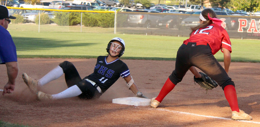 ROSS MARTIN/Citizen photo Park Hill South junior Kate Kobayashi, left, slides safely into third base while Park Hill third baseman Alexa Lashbrook takes a throw in a game Monday, Oct. 2 at Park Hill High School in Kansas City, Mo.